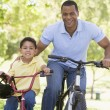Man and young boy on bikes outdoors smiling - Stock Photo