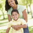 Woman and young boy outdoors embracing and smiling — Stock Photo
