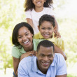 Family lying outdoors smiling — Stock Photo #4768125