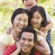 Family lying outdoors smiling — Stock Photo