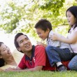 Family lying outdoors being playful and smiling — Stock Photo