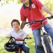 Man and young boy on bikes outdoors smiling — Stock Photo #4768148