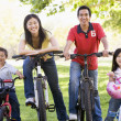 Family on bikes outdoors smiling - Stock Photo