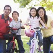 Family with children on bikes outdoors smiling — Stock Photo
