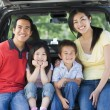 Family sitting in back of van smiling — Foto Stock