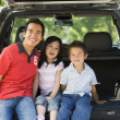Man with two children sitting in back of van smiling — Stock Photo