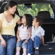 Woman with two children sitting in back of van smiling - Stock Photo