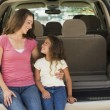 Woman with young girl sitting in back of van smiling — Stock Photo