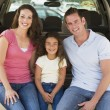 Family sitting in back of van smiling — Stock Photo
