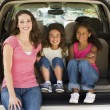 Woman with two young girls sitting in back of van smiling — Stock Photo #4768175