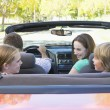 Family in convertible car smiling - Stock fotografie