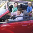Foto Stock: Family in convertible car smiling