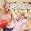 Woman and young girl in bowling alley holding ball and smiling - Stock Photo