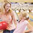 Woman and young girl in bowling alley holding ball and smiling — Stock Photo