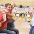 Royalty-Free Stock Photo: Family in bowling alley cheering and smiling