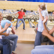 Family in bowling alley with two friends cheering and smiling — Stock Photo #4768205