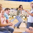 Family in bowling alley with two friends cheering and smiling — Stock Photo #4768208