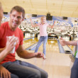 Family in bowling alley cheering and smiling — Stock Photo