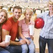 Family in bowling alley with drinks smiling - Stock Photo