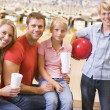 Family in bowling alley with drinks smiling — Stock Photo
