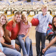 Family in bowling alley with two friends smiling - Stockfoto