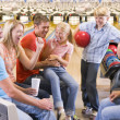 Family in bowling alley with two friends cheering and smiling — Stock Photo #4768217