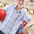 Young boy in bowling alley holding ball and smiling - Stockfoto