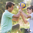 Man and young boy outdoors holding soccer ball and smiling - Stock Photo