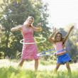 Woman and young girl outdoors using hula hoops and smiling — Stock Photo