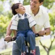 Man and young boy on a bike outdoors smiling — Stock Photo #4768225