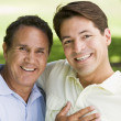 Two men outdoors embracing and smiling - Stockfoto