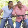 Two men on bikes outdoors smiling - Stock Photo