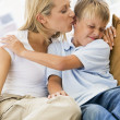 Woman kissing disgusted young boy in living room - Stock Photo