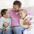 Man and two children sitting in living room smiling — Stock Photo #4768280