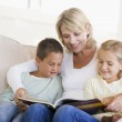 Woman and two children sitting in living room reading book and s — Stock Photo #4768282