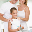 Couple in bathroom with young boy brushing teeth — Stock Photo #4768287