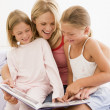 Woman and two young girls in bedroom reading book and smiling — Stock Photo