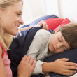 Woman waking young boy in bed smiling — Stock Photo