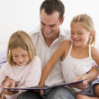 Man in bedroom with two young girls reading book and smiling — Stock Photo