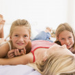 Woman lying in bed with two young girls smiling — Stock Photo