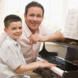 Man and young boy playing piano and smiling — Stock Photo #4768320