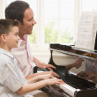 Stock Photo: Mand young boy playing piano and smiling