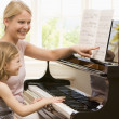 Woman and young girl playing piano and smiling - Stock Photo