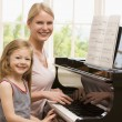 Woman and young girl playing piano and smiling — Stock Photo #4768323