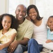 Family sitting in living room smiling — Stock Photo #4768324