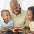 Man and two children sitting in living room reading book and smi - Stock Photo