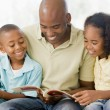 man and two children sitting in living room reading book and smi — Stock Photo