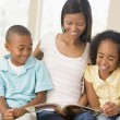 Woman and two children sitting in living room reading book and s - Stock Photo