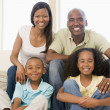 Stock Photo: Family sitting in living room smiling