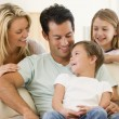 Family sitting in living room smiling — Stock Photo #4768334